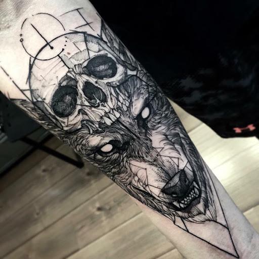 Um crânio e o lobo temáticos manga da tatuagem. Você pode ver o crânio humano que está sendo usado como um chapéu pela raiva olhando lobo. A tatuagem parece bem feito e destemido e definitivamente não é para os fracos de vontade.