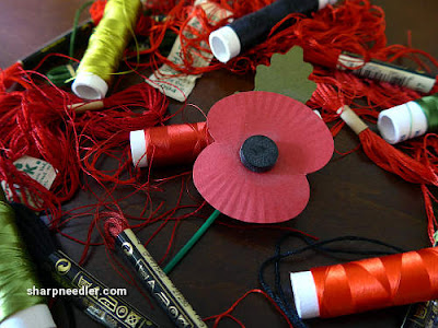 Silk and cotton threads surround a paper remembrance poppy