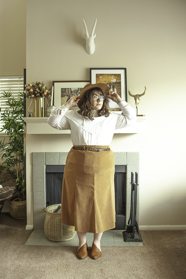Brown panama hat, white blouse with lace and pleats on the front tucked into a brown maxi skirt belted with a brown belt and brown d'orsay flats.