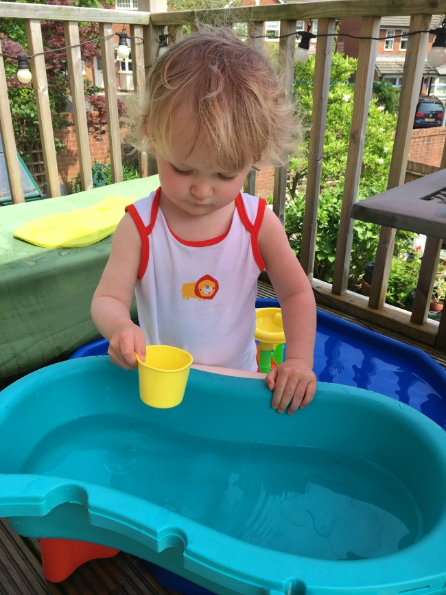 toddler in vest playing with water in the shade