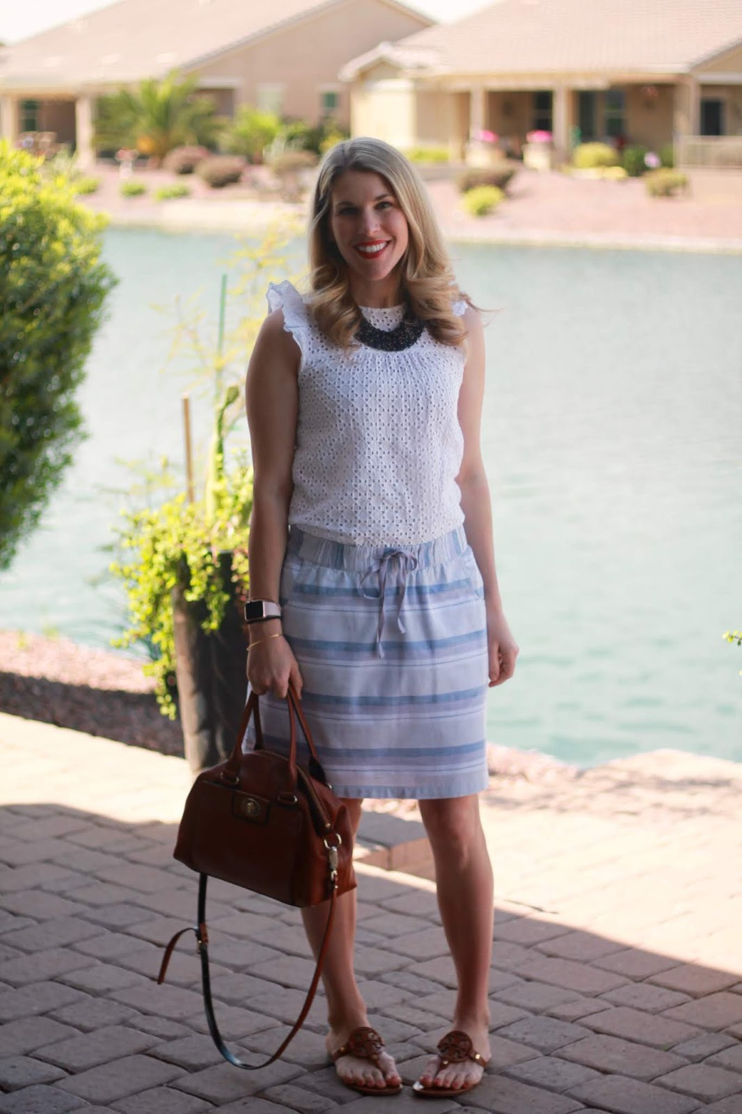 white eyelet blouse, aventura grey and blue striped skirt, tory burch miller sandals, cognac crossbody bag
