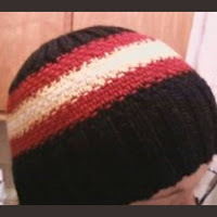 A black beanie in 2x2 rib with red, yellow, and white stripes knit in linen stitch
