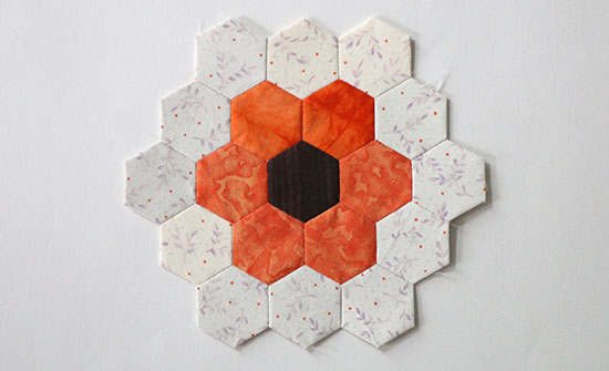 Top view of an EPP hexagon flower block in dark brown, orange, light purple and off-white on a white background.