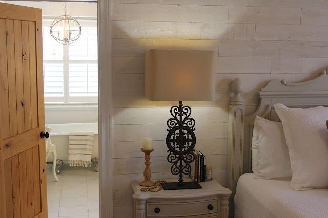 Knotty alder door open to white modern farmhouse style bathroom renovation by Hello Lovely Studio