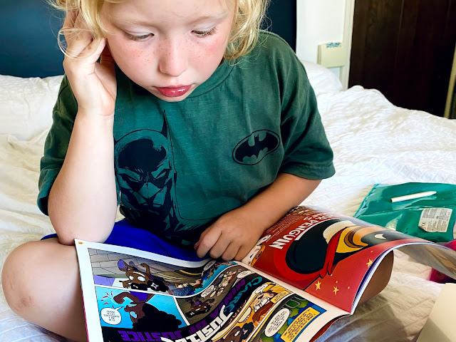 A girl sitting on a bed reading the phoenix comic