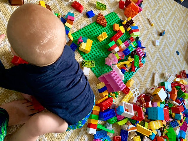 Baby in a cloth nappy next to a big pile of LEGO DUPLO