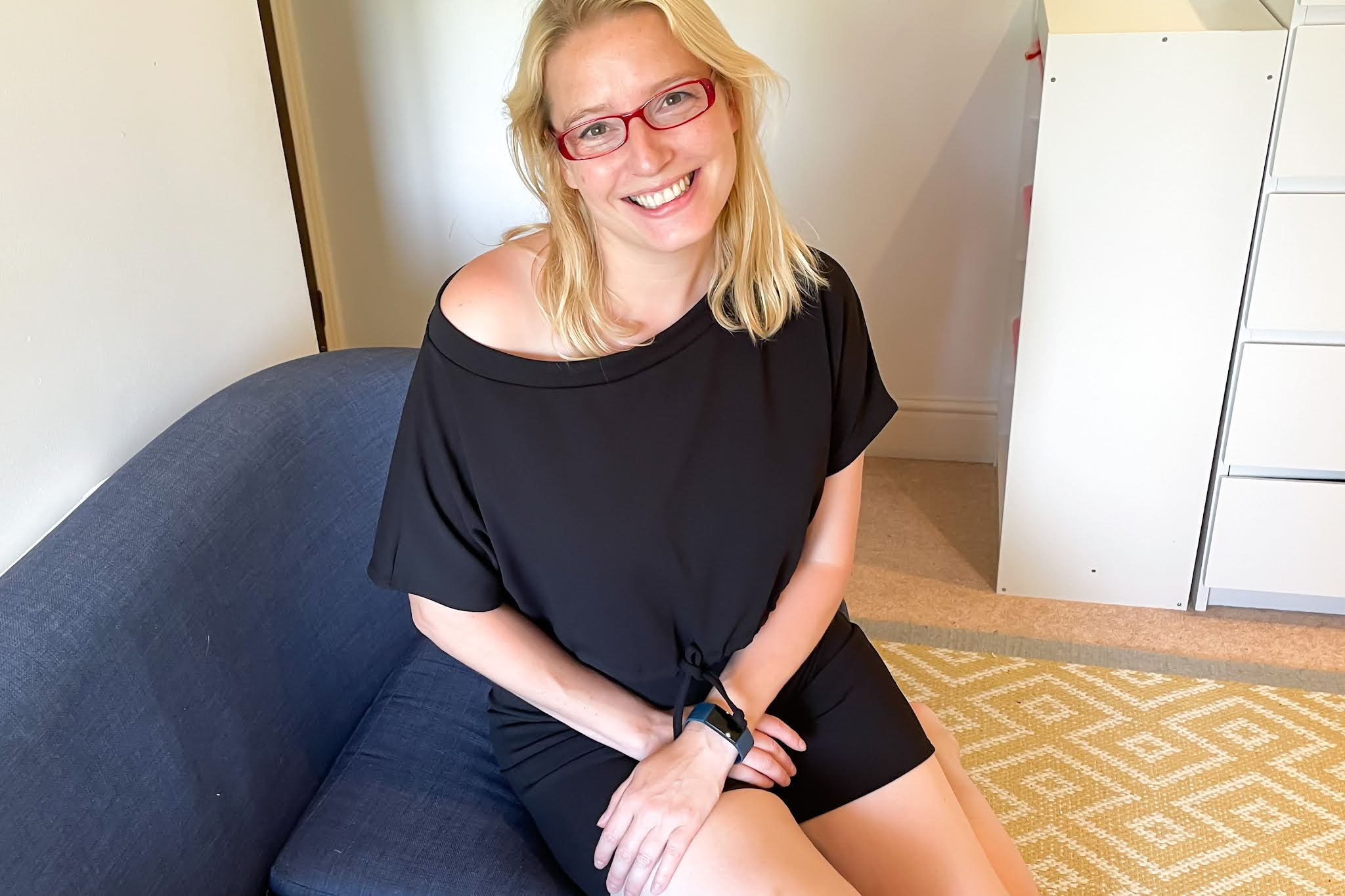 Sitting on a sofa wearing a black top and shorts and smiling to be happy wearing black