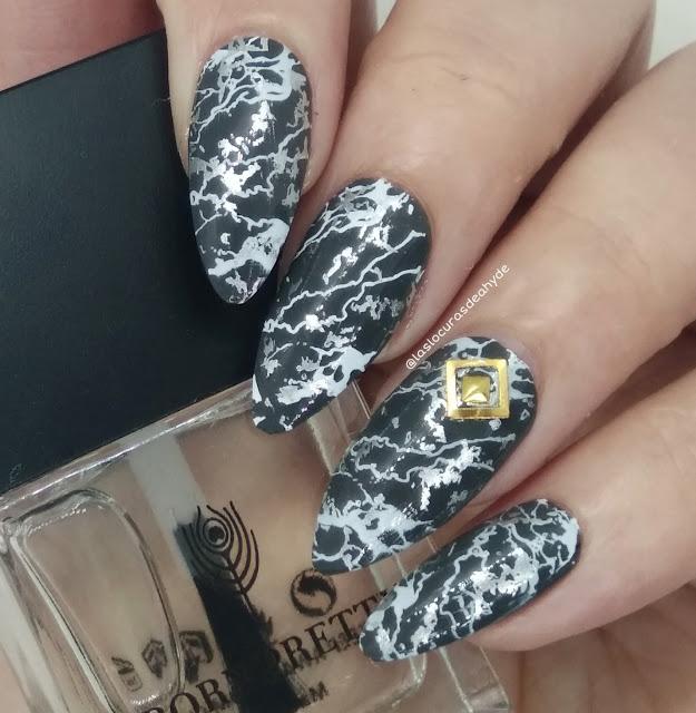 nail art con efecto marmol en colores gris y blancos, anular decorado con dos piezas doradas