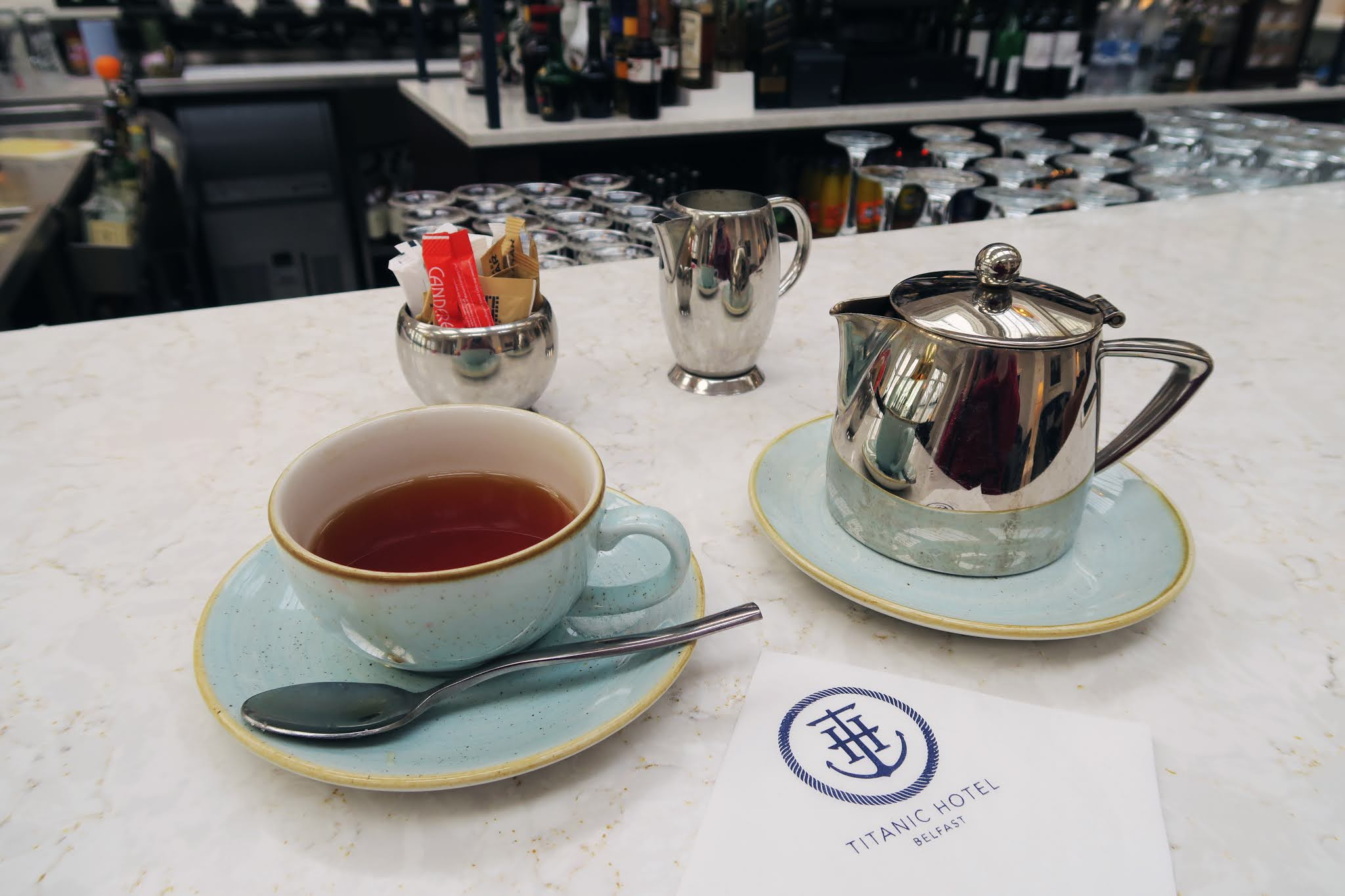A cup of tea and a matching blue teapot on the bar in the Drawing Room Two inside the Titanic Hotel