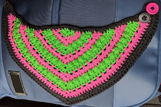 Crochet bib in pink and green finished with a black border.