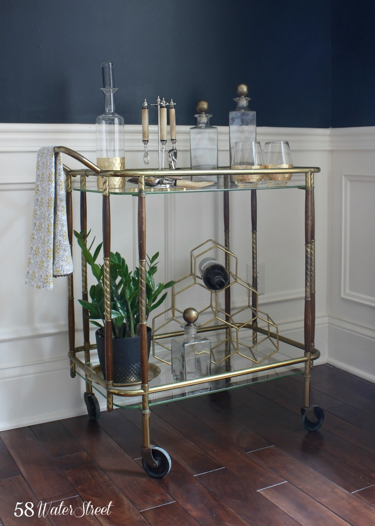 navy blue dining room with vintage brass details and vintage bar cart