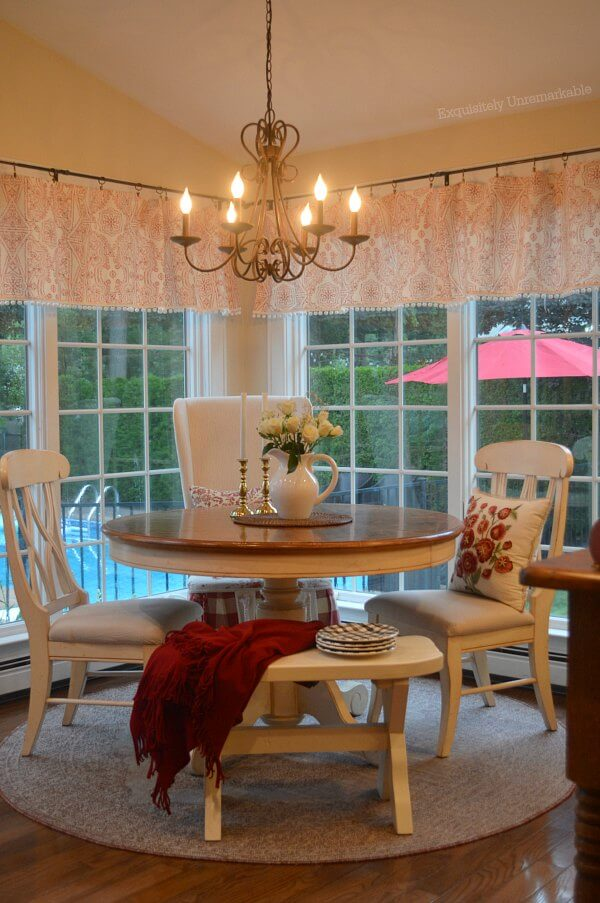 Cozy Cottage Kitchen Nook with round table, upholstered chair and kitchen bench