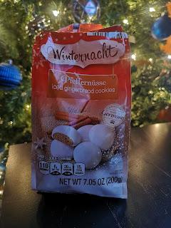 Bag of Winternacht Pfeffernusse Iced Gingerbread Cookies, against a Christmas tree backdrop