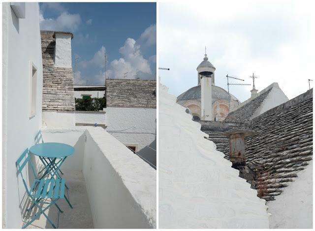 Vistas desde la terraza del apartamento. A la izquierda mesa con sillas azules y a la derecha tejados grises.