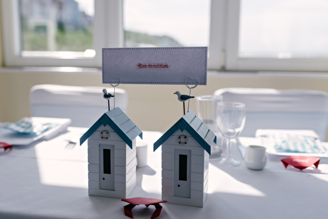 Vintage seaside wedding - top table beach hut table name card holders