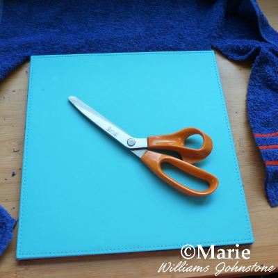 trim excess surplus towel fabric away from bottom of mat