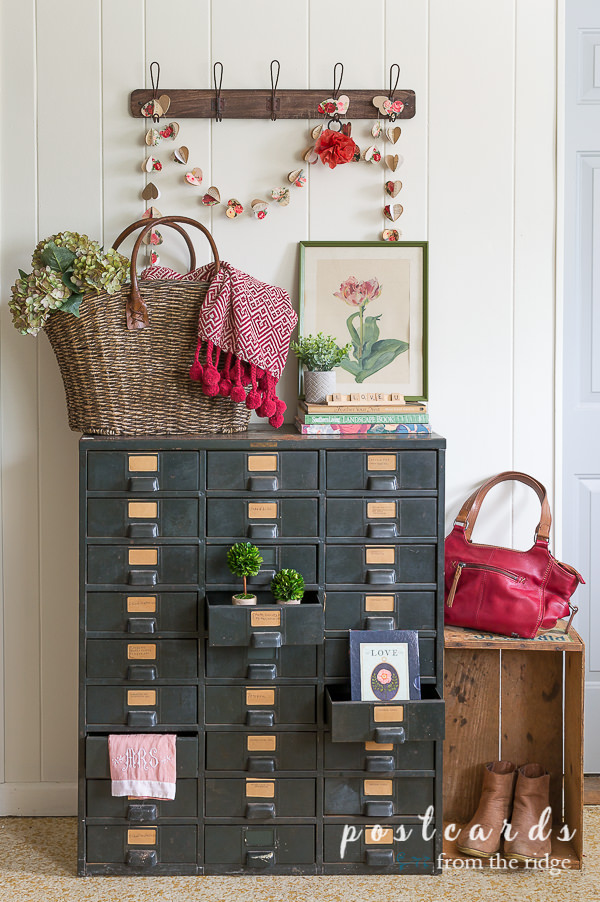 paper heart garland and vintage metal drawer cabinet with various valentine's day decor