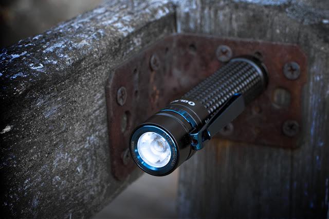 Olight S2R BatonII przymocowana do stalowego kątownika przy pomocy wbudowanego magnesu
