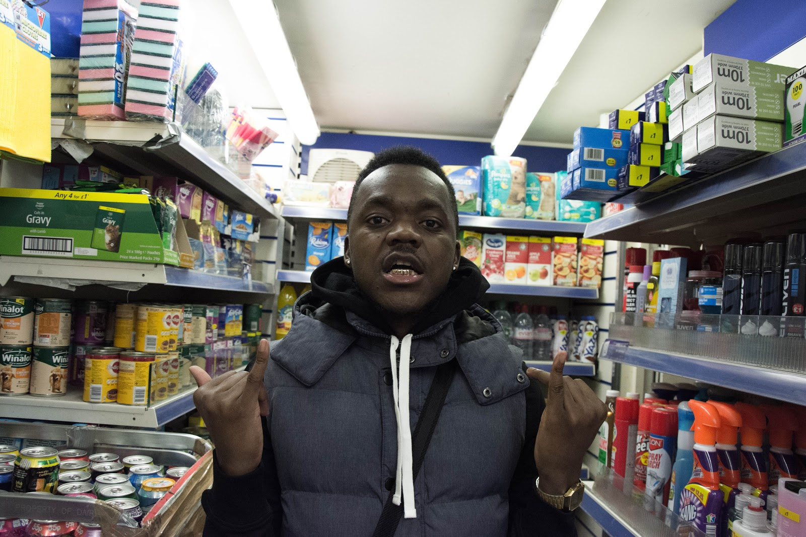 Pictured is J-Zino, wearing a black/grey jacket and standing in a store.