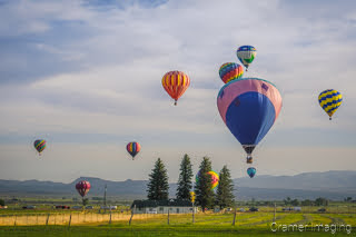 Cramer Imaging's fine art photograph of a hot air balloon cluster drifting over a field in Panguitch Utah with a blue partly cloudy sky