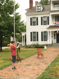 Female photographer in red shirt and black capris photographing a red chair on the brick sidewalk in front of a historic two-story mansion
