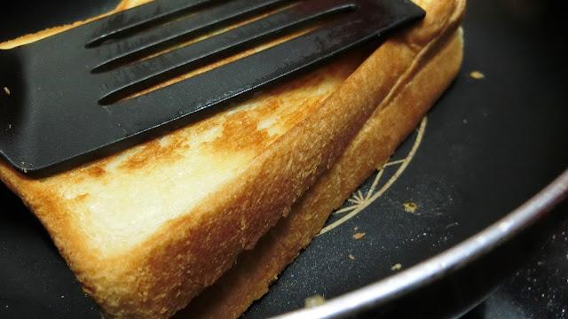 フライ返しで食パンを押し付ける時、少し強めに力を入れます。 こうすることで、熱で溶けたチーズが他の食材にしっかりくっつき、食べる時にバラバラとはがれる心配がありません。