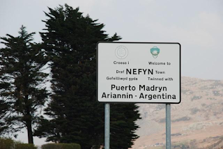 A black and white road sign gives place names in Spanish and Welsh. Trees and a mountainside are glimpsed behind it.