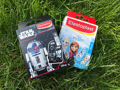 A box of Elastoplast Star Wars Plasters and Elastoplast Frozen Plasters on green grass