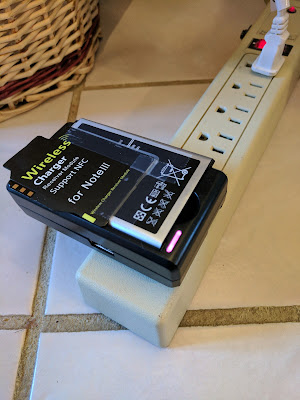 The external battery charger does not interfere with the wireless receiver coil card taped to the spare battery.
