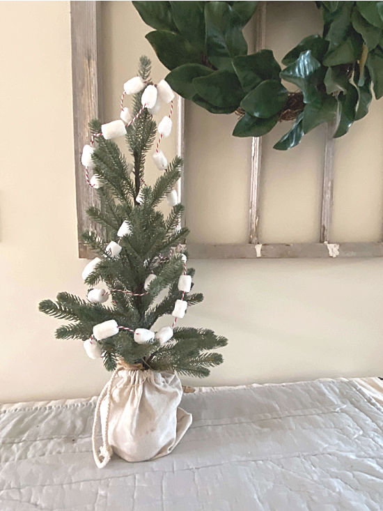 small tree in front of chippy window with wreath