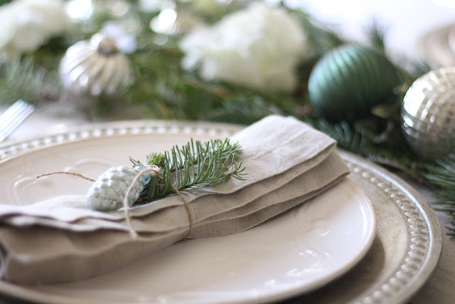 holiday tablescape with linen napkins white plates silver chargers ornaments christmas