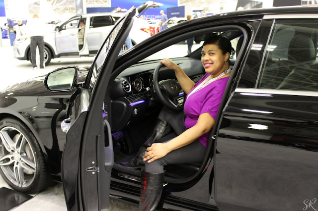 A picture of a lady inside a black Mercedes Benz at the auto show