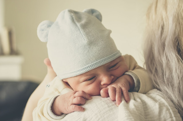 Photo on newborn weting a hat on mom's shoulder