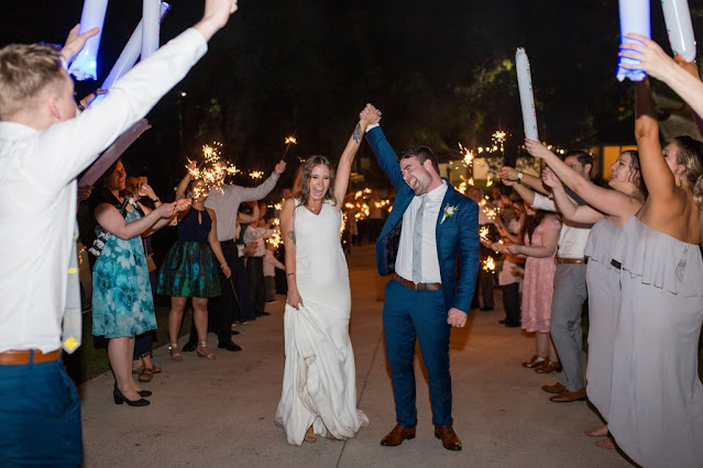bride and groom at baby gender reveal during wedding exit