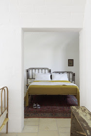 White bedroom with ochre coloured bedding