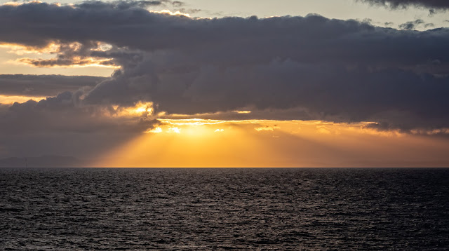 Photo of a wider view of the sun setting over the Solway Firth
