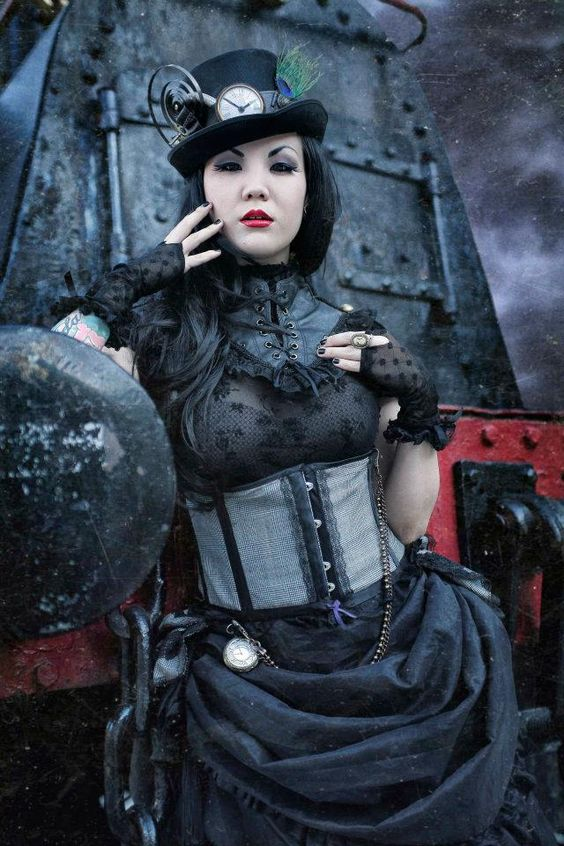 Steamgoth woman (gothic steampunk). Clothing: corset, black lace blouse, black skirt, black lace fingerless gloves, top hat. Jewelry: cameo ring, pocket watch. Makeup: purple eyeshadow, red lipstick