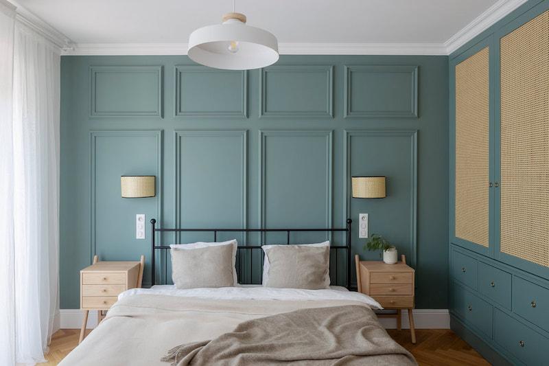 Dormitorio doble con cama de hierro y pared pintada de verde oliva con escayola decorativa.