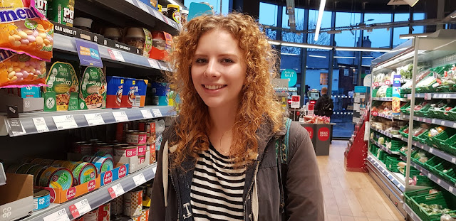 Young woman smiling and shopping in co-op supemarket