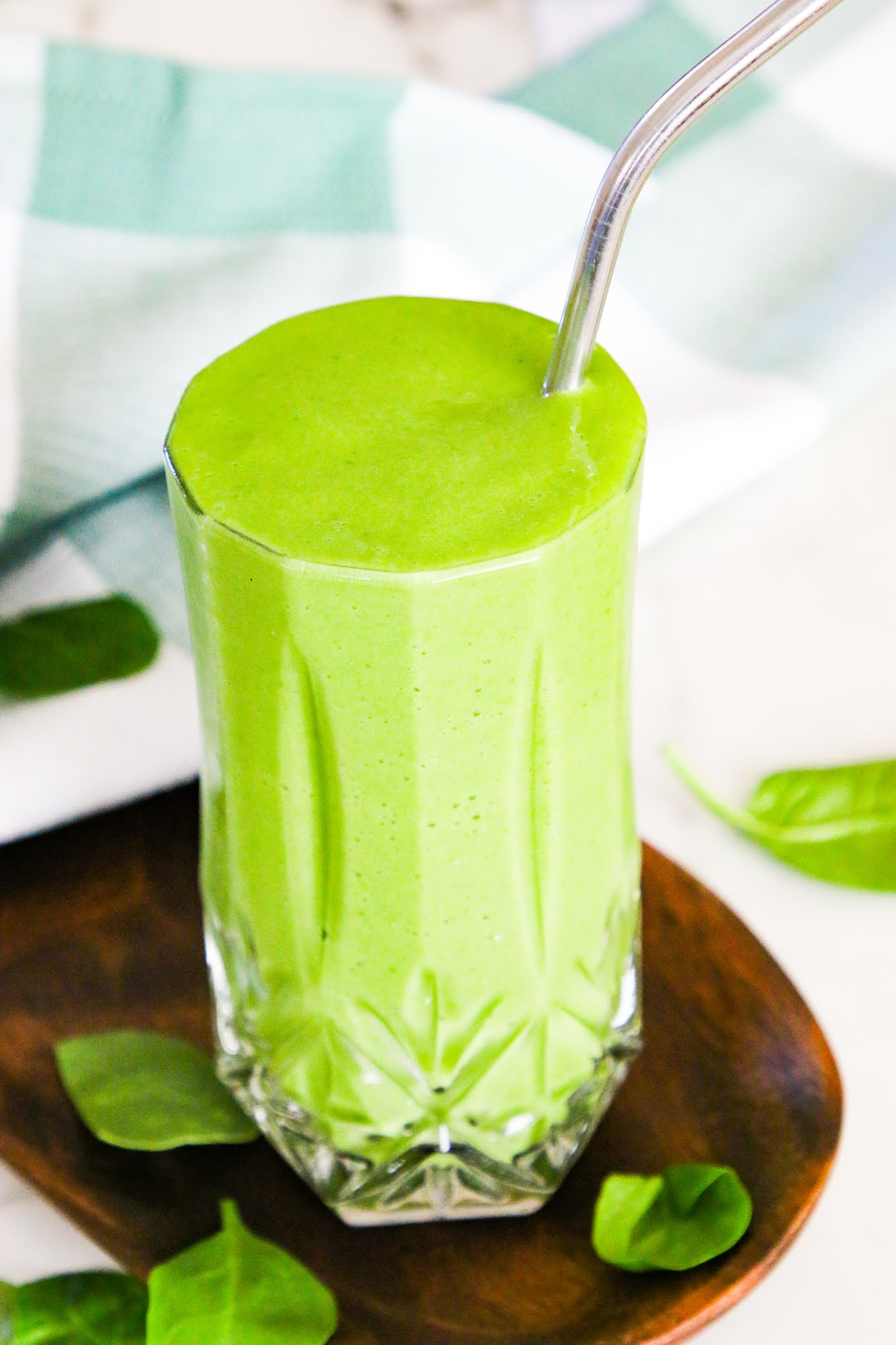 Mango Kale Green smoothie on a wooden coaster with a green dish towel in the background on a marble table