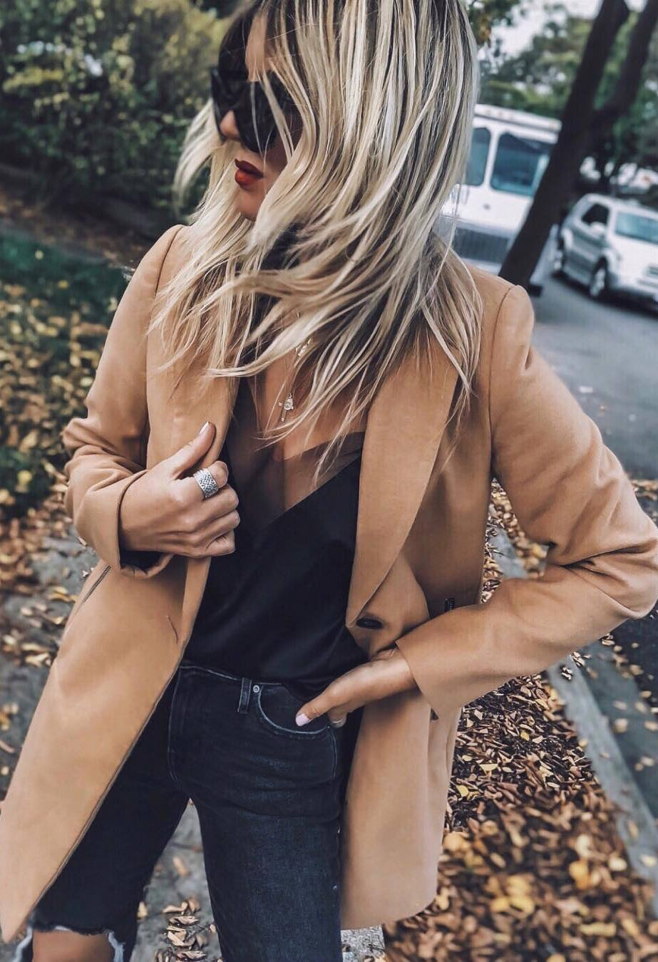 what to wear with a black silk top : brown coat and jeans