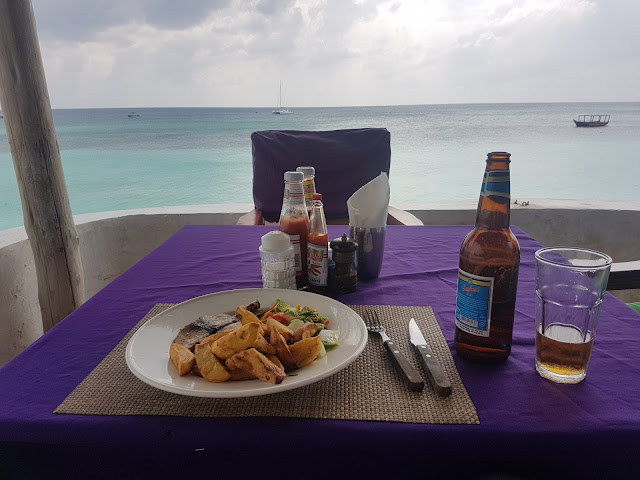 A plate of chips and seafish, with a bottle of Safari beer on a table set on Copa Cabana's balcony overlooking the ocean
