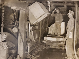Black and white photo of two miners underground, both wearing safety helmets with lamps, one standing on a coal car