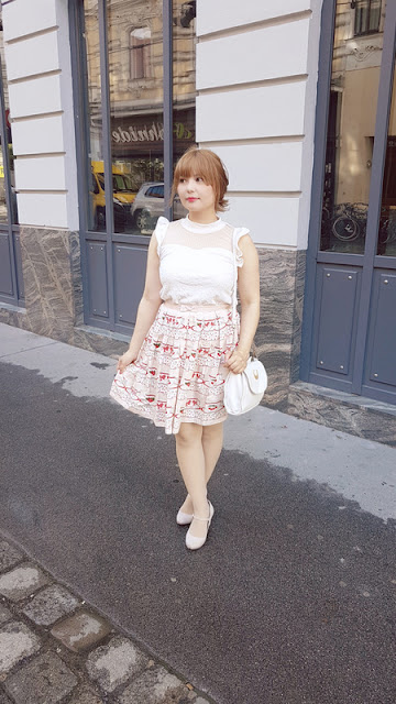 picture on the street of auris wearing a tea skirt and a white liz lisa blouse