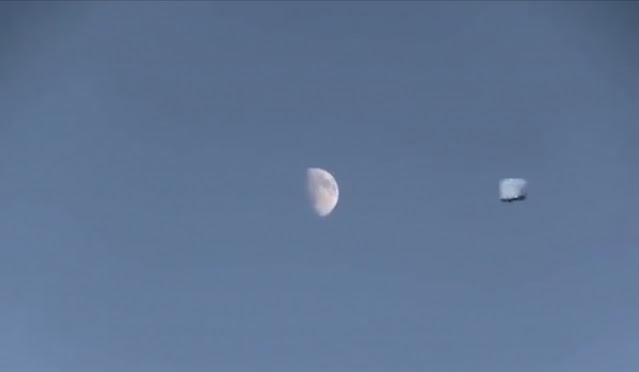 This cube UFO looks epic passing the Moon.