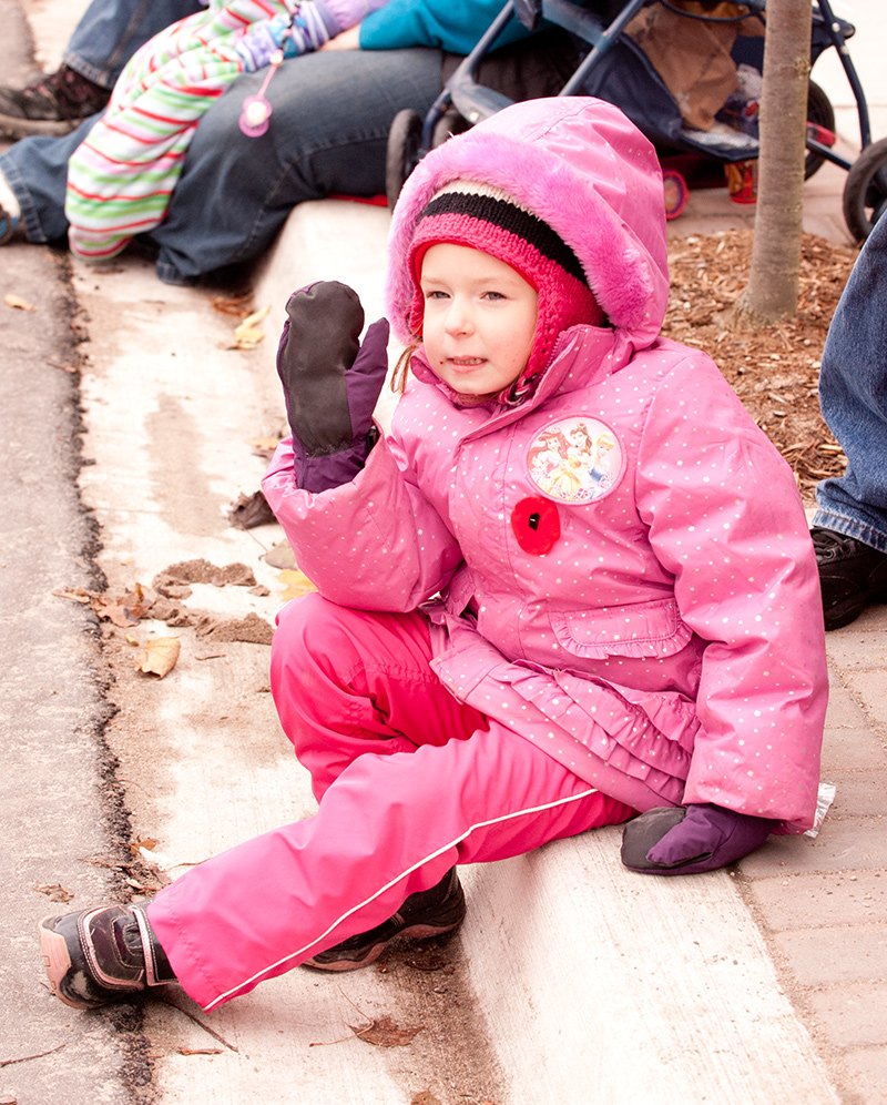A five year old girl wearing pink snowsuit enjoying the Santa Clause Parade
