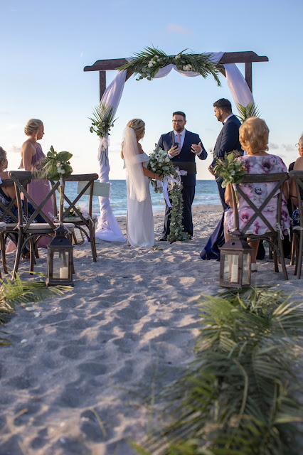 Bride and groom under floral arch in island ceremony.