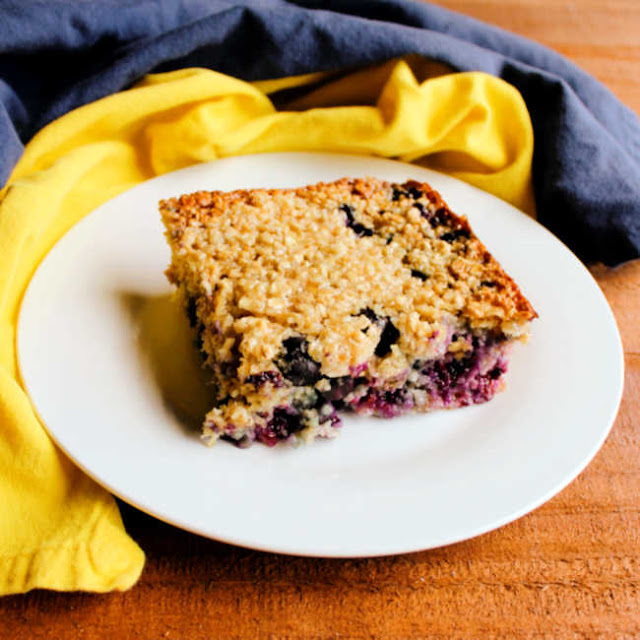 piece of lemon and blueberry baked oatmeal on small plate with blue and yellow napkins nearby