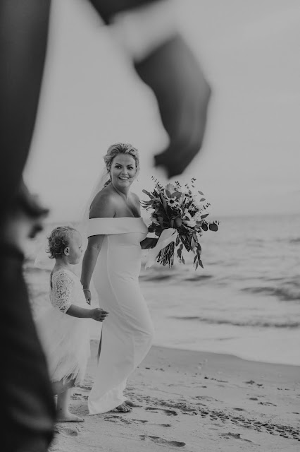 Bride and flower girl candid photos walking down the beach.