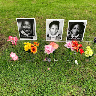 Black and white headshots of Carole Robertson, Addie Mae Collins, and Denise McNair, displayed on the lawn with flowers